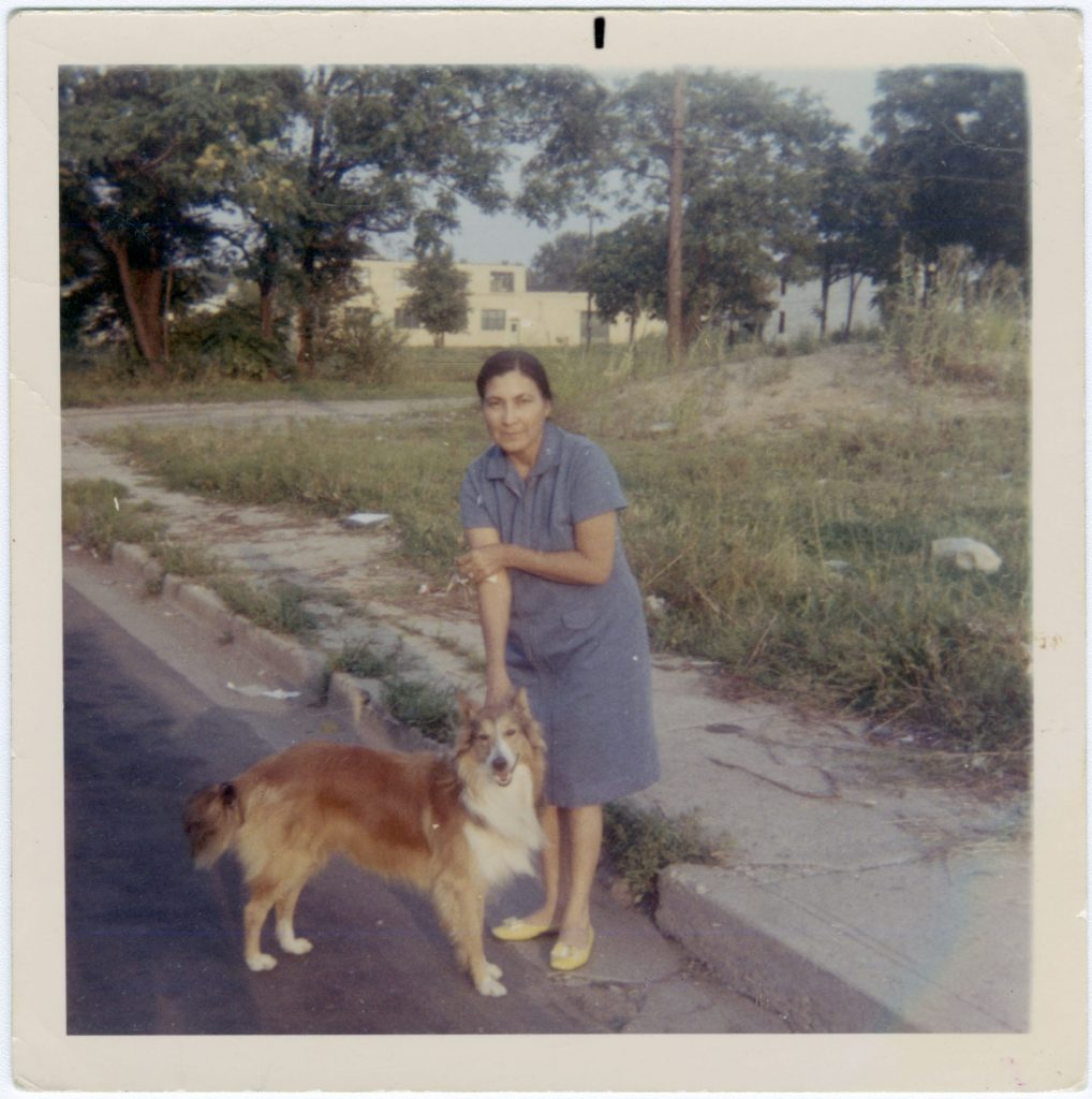 Maria Espinoza with family dog, Duke on North Street ca. 1960s