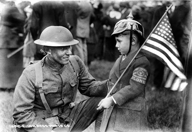 A soldier wearing a helmet kneels beside a boy who carries an American flag. The little boy also wears a helmet and has a patch on his coat sleeve. The soldier is identified as Charles Robinson of Madison, Indiana.